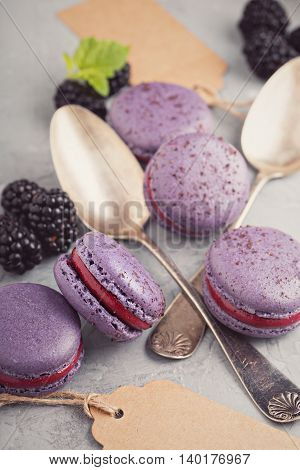 French macarons with berry filling on a gray table toned picture