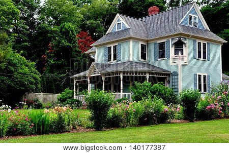 Sandwich Massachusetts- July 13 2015: Victorian-era home with large front porch gables and Summer flower garden