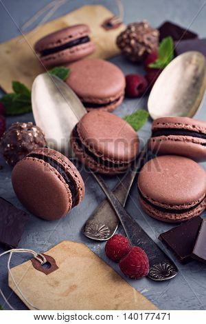 Chocolate french macarons with ganache filling on a gray table