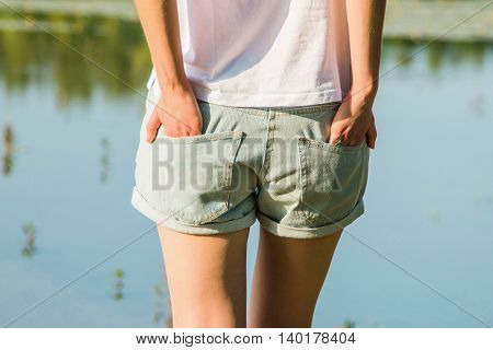 Young woman in shorts on lake from behind, body detail