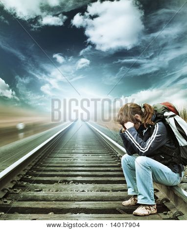 Alone woman sitting on railroad under blue sky