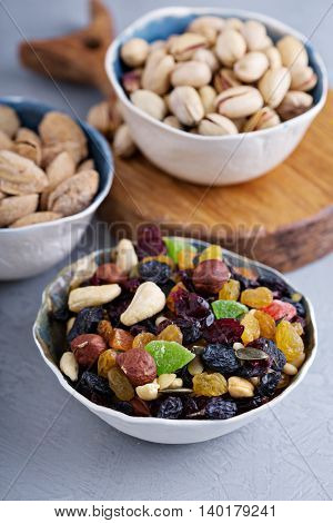 Mixed nuts and fruits in a bowl including raisins, pine nuts, cashews