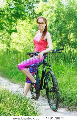 Sports Woman With A Bike On The Walk