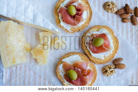 Delicious bruschetta with prosciutto and olives with cheese Parmesan and Bree, and nuts. Italian appetizer. Top view.