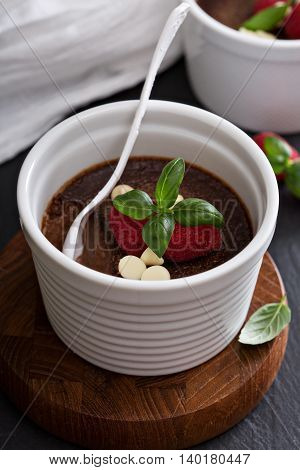 Chocolate pudding with raspberries and basil baked in ramekins