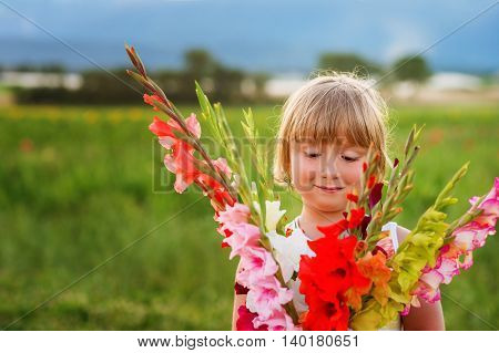 Beautiful bouquet of bright and colorful gladiolas flowers holding by cute little boy