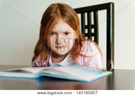 Interior portrait of an angry little girl doesn't want to read book