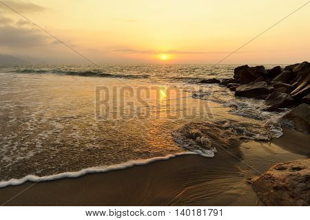 Ocean sunset is a a seascape with sea water moving through sand and rocks as the orange sun sets on the ocean horizon.