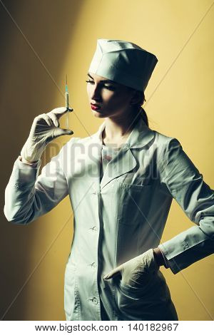 Beautiful young doctor in medical uniform holding syringe with liquid on yellow background