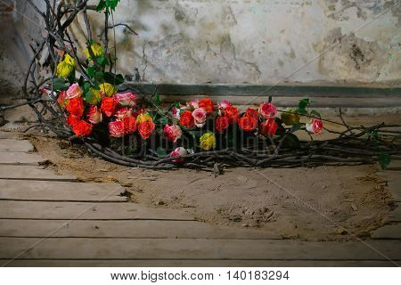 Floral arrangement with colorful rose flowers and wooden twigs on wood floor copy space