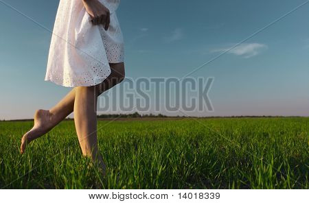 Young woman in white dress walking on meadow with green grass