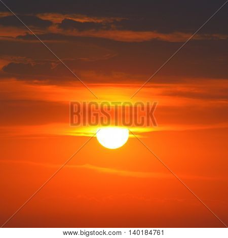 Bright sun on a background of red sky and clouds.