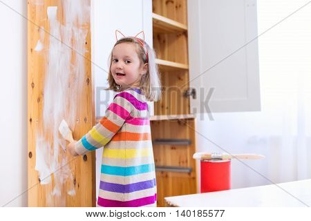 Happy preschool age girl holding a brush painting a wooden bedroom closet with white color paint. Child learning furniture renovation and restoration. Do it yourself project with kids at home.