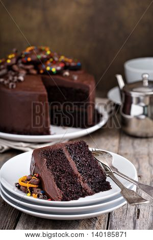 Slice of chocolate cake with glaze and ganache decorated with donuts