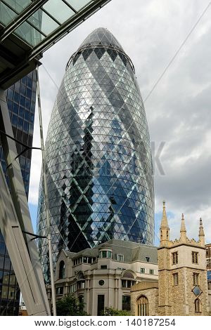 LONDON UK - JULY 1 2014: The modern 30 St Mary Axe called Swiss Re Building or informally the Gherkin in the City of London one of the leading centers of global finance.