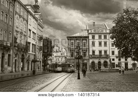 LVIV UKRAINE - MAY 8 2016: The center of Lviv - The Market Square. Two trams passing along the street. Black and white photo. Ukraine
