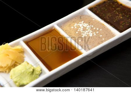 japanese sauces wasabi and ginger on black table