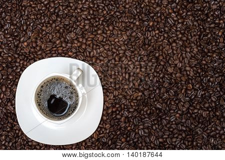 coffee beans background and white cup with hot drink