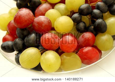 Closeup of bright tasty ripe grapes in a glass plate