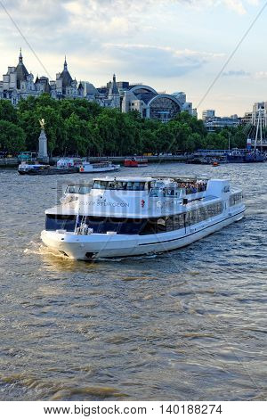 LONDON UNITED KINGDOM - JULY 1 2014: A City Cruises tour boat sails on the Thames River near Westminster. Thames is the longest river in England with 346 km in length.