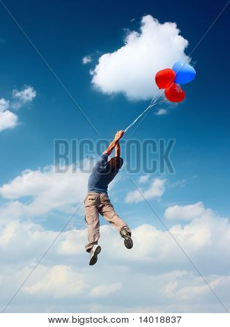 Man with balloons flying in blue cloudy sky