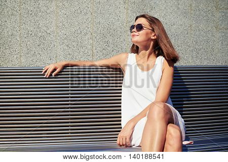 Young beautiful lady in sunglasses is sitting on a bench in the street and enjoying the warmth of summer sunlight