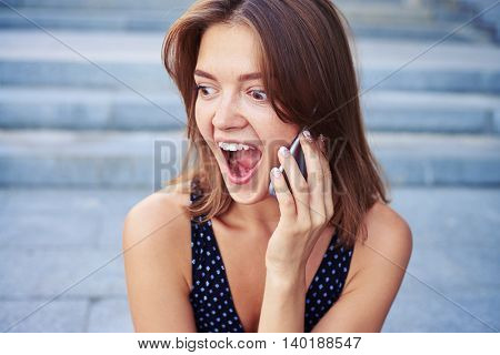 Beautiful lady is listening to her phone interlocuter with the surprised expression on her face over street stairs background