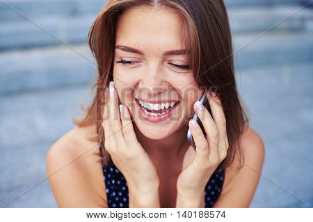 Close-up of  beautiful girl talking on the mobile phone with a broad smile on her face and looking down