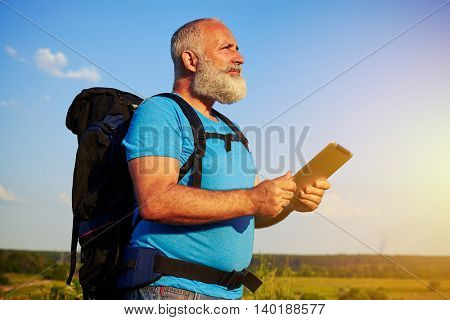 Handsome aged man with rucksack holding a data tablet and looking into the distance on the background of blue sky in the field