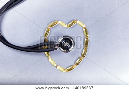 Healthy heart concept with fish oil capsules and stethoscope on stainless steel.