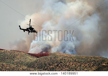 Helicopter Flying Toward the Dense White Smoke Rising from the Raging Wildfire