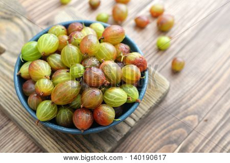 Fresh ripe gooseberries in bowl on a wooden background closeup