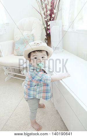 Adorable Asian baby boy next the window lights