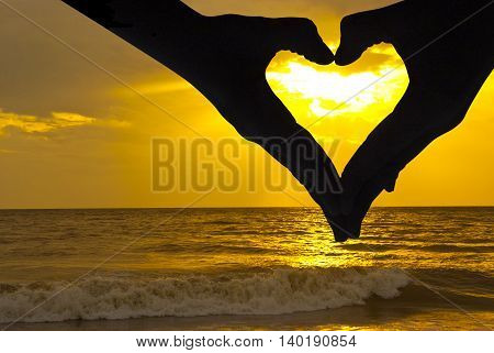 Beautiful sunset above the sea and hands whit love signal