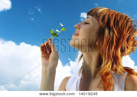 Woman with red hair smelting flower on meadow