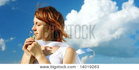 Young woman with flower and blue sky with clouds