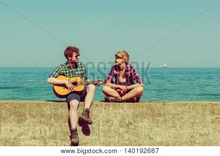 Young man playing guitar to his girlfriend outdoor sunny summer day by seaside- dating romantic couple