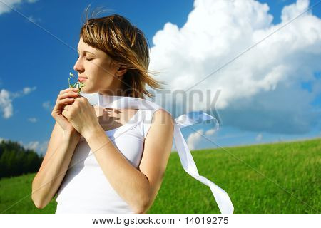 Young woman smelting flower and blue sky with clouds