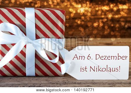 Macro Of Christmas Gift Or Present On Atmospheric Wooden Background. Card For Seasons Greetings Or Congratulations. White Ribbon With Bow. German Text Am 6. Dezember Ist Nikolaus Means Nicholas Day