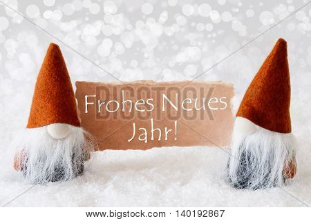 Christmas Greeting Card With Two Bronze Gnomes. Sparkling Bokeh Background With Snow. German Text Frohes Neues Jahr Means Happy New Year