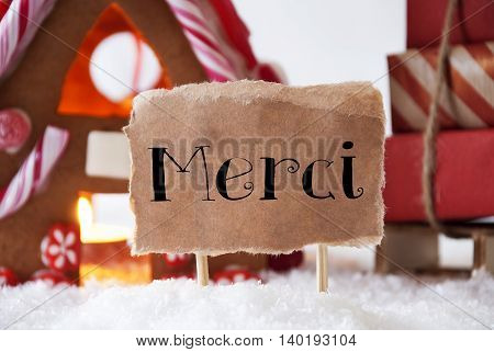 Gingerbread House In Snowy Scenery As Christmas Decoration. Sleigh With Christmas Gifts Or Presents. Label With French Text Merci Means Thank You