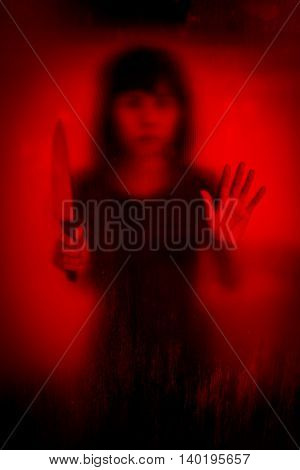 Horror scene of woman with knife behind stained or dirty window glass,Serial killer or violence concept backgroun