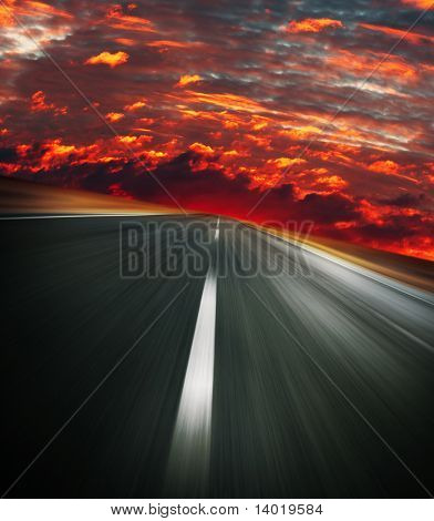 Blurred asphalt road and red bloody sky