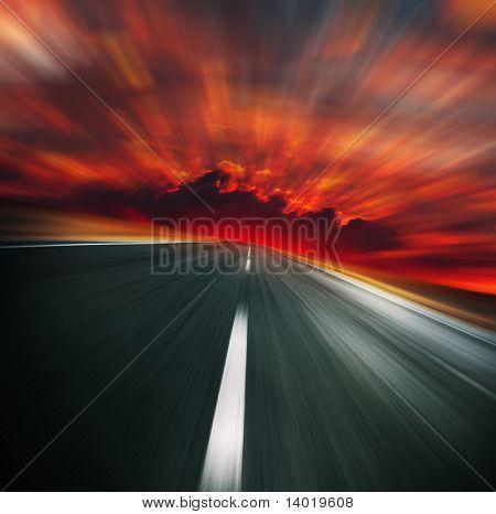 Carretera asfaltada borrosa y cielo rojo sangriento borrosa