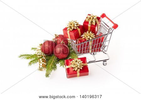 Shopping trolley with gift boxes and brenches of fir-tree with decoration on a white background. Christmas and New Year sale.