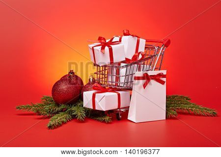 Shopping trolley with gift boxes and brenches of fir-tree with decoration on a red background. Christmas and New Year sale.