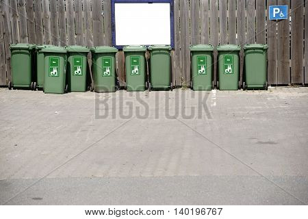 A number of green recycling bins for glass waste is facing a wooden fence.