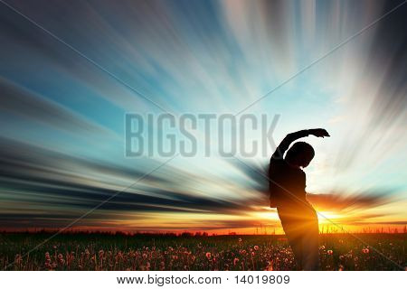 Young woman standing on meadow with herbs under sunset lights