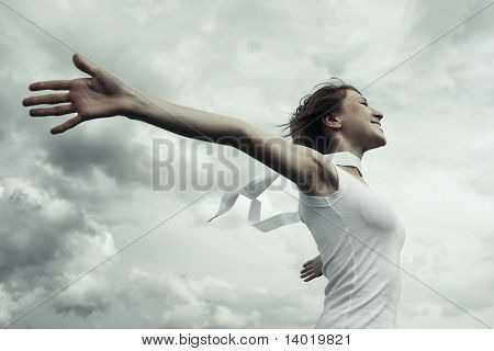 Young woman with raised hands over clouds background