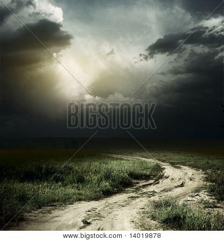 Ländlichen Straßen- und dunkle Gewitterwolken